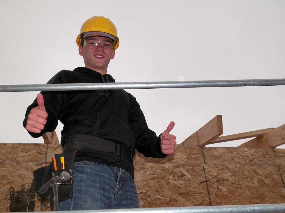 Building Construction student wearing a hardhat gives thumbs up