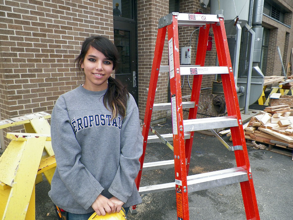 Building Construction student holds her hardhat while standing by a ladder