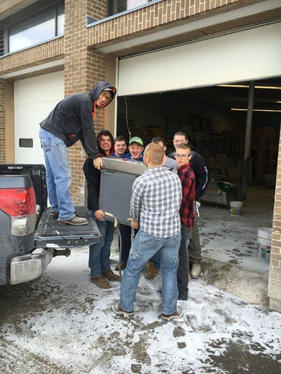Building Construction students unload equipment from a truck