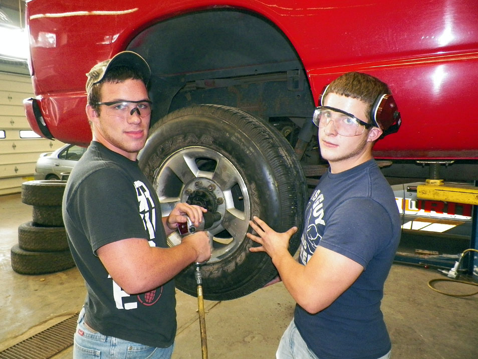 Automotive Technology students working on a tire