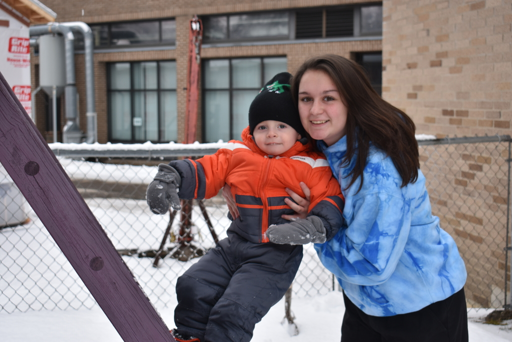 Child and Family Services student helps a child up a ladder
