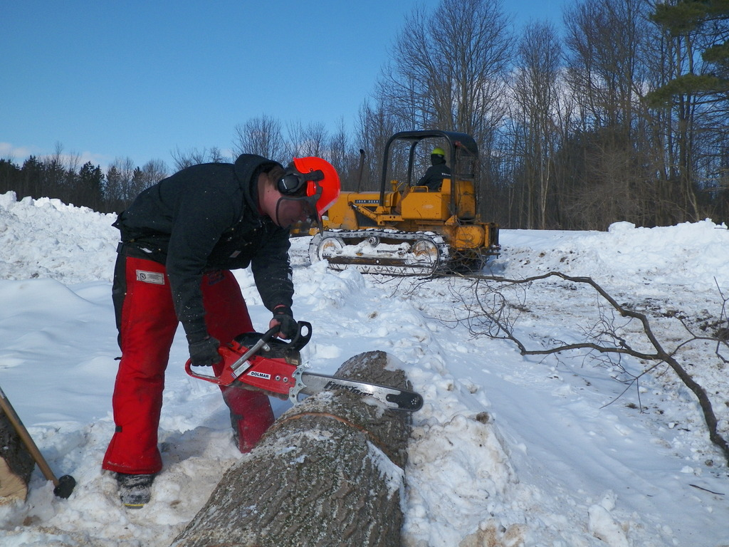 Student cuts a log while another student plows snow