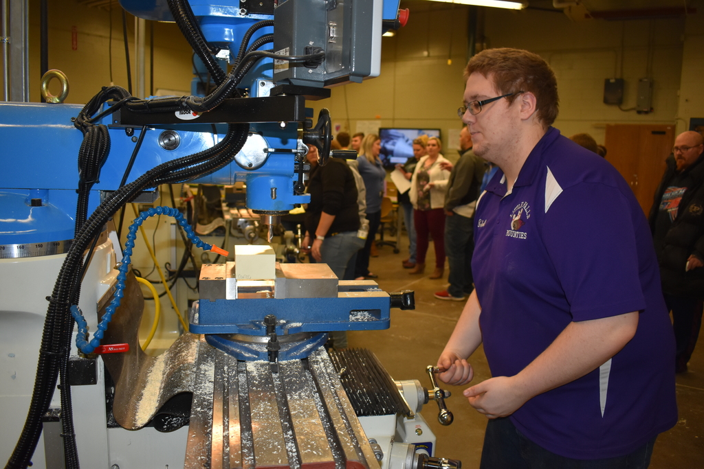 Student operates an advanced manufacturing machine