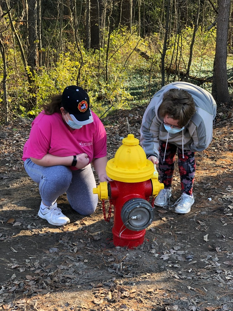 Students painting a fire hydrant red and yellow