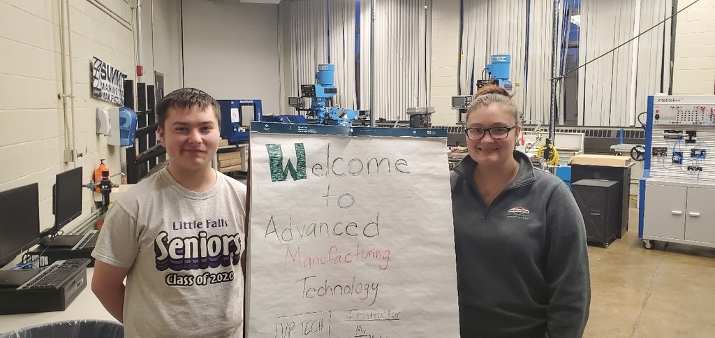 advanced manufacturing students by a sign for class