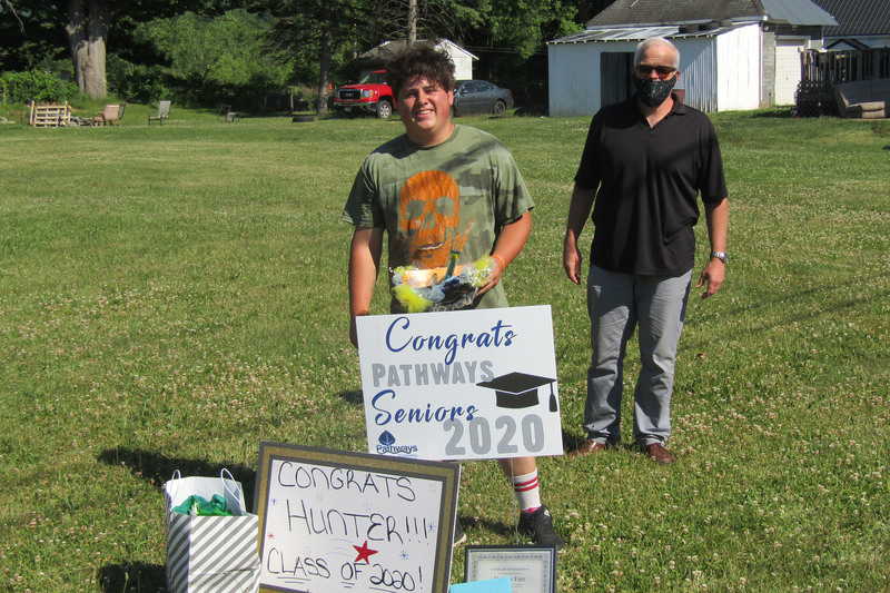 Pathways student holding a sign delivered during Senior Recognition Caravan with Patrick Corrigan standing in back