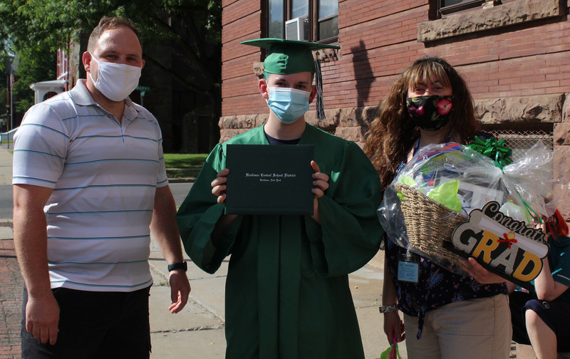 Student in cap and gown holds up a diploma next to Tim Johnston and another person during Senior Recognition Caravan
