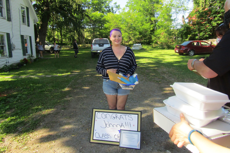 Students next to a sign and a diploma with food about to be handed to her during senior recognition caravan