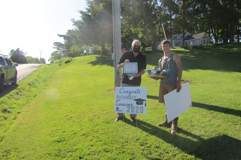 Student posing outside with Pathways Principal Patrick Corrigan holding signs and a diploma